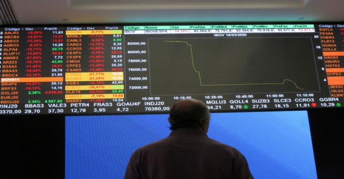 FILE PHOTO: A man stands in front of an electronic display at B3 Brazilian Stock Exchange after