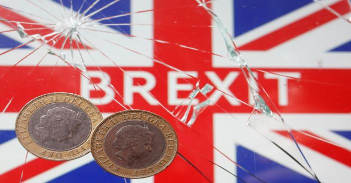 FILE PHOTO: A pound coins are placed on broken glass and British flag in this illustration