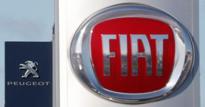 The logos of car manufacturers Fiat and Peugeot are seen in front of dealerships of the