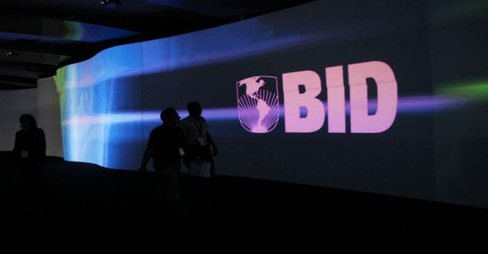 FILE PHOTO: Visitors walk past a screen with the logo of Banco Interamericano de Desarrollo at
