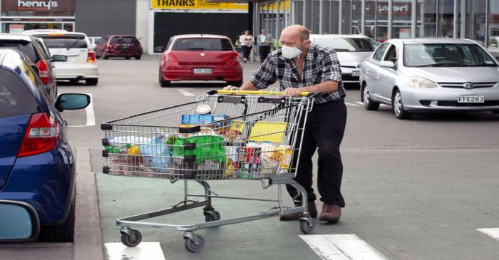Brian Green, 76, wears a mask as he wheels his supermarket shopping cart to his car outside