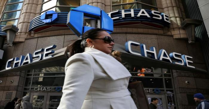 FILE PHOTO: A woman passes by a JPMorgan Chase bank in Times Square in New York