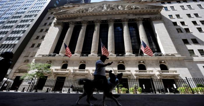 FILE PHOTO: A man walks a dog in the shade past the New York Stock Exchange (NYSE) during hot