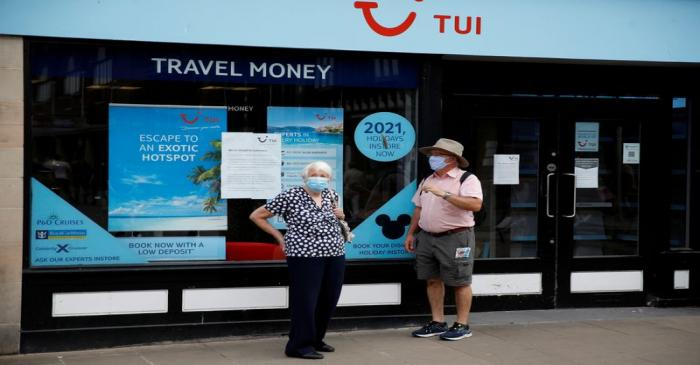 FILE PHOTO: People wear face coverings as they stand outside a Tui travel agents shop following