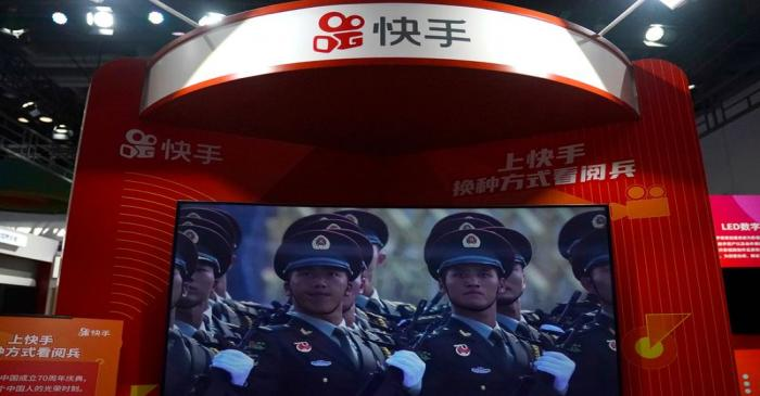 FILE PHOTO: A screen showing footage of a military parade is seen at a booth of Chinese