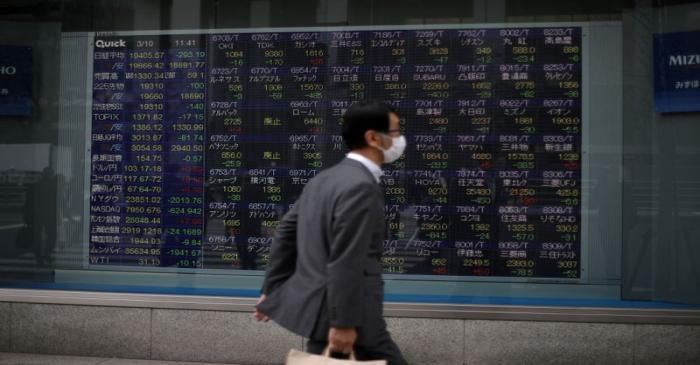 FILE PHOTO: A man wearing protective face mask walks in front of a stock quotation board