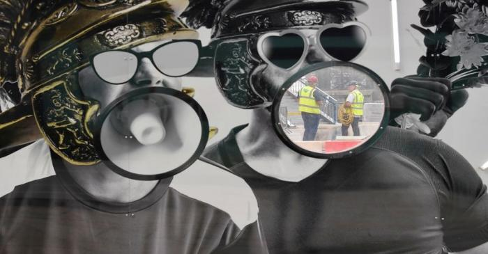 Workers are seen through a viewing hole on perimeter boarding around a construction site, in