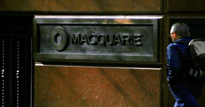 FILE PHOTO: A pedestrian walks past the logo of Australia's biggest investment bank Macquarie