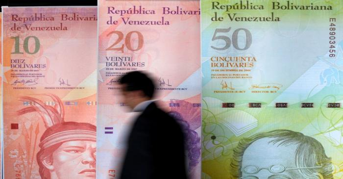 FILE PHOTO: A man walks past big samples of Venezuelan bank notes at the Central Bank