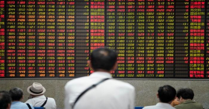 People look at an electronic board showing stock information at a brokerage house in Shanghai