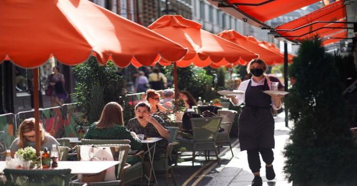 FILE PHOTO: People sit at tables outside restaurants in Soho, amid the coronavirus disease