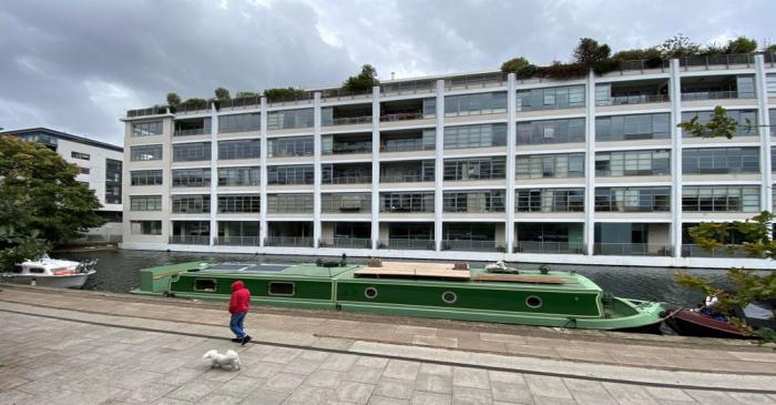 A person walks their dog past a canal boat and a block of flats in London