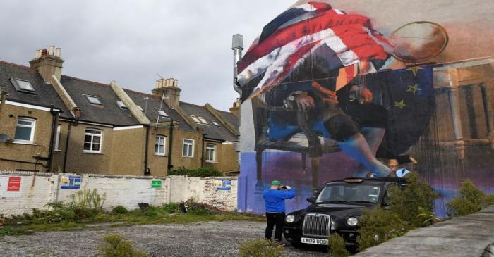 FILE PHOTO: A man records an image of a recently painted mural of a person sitting with both