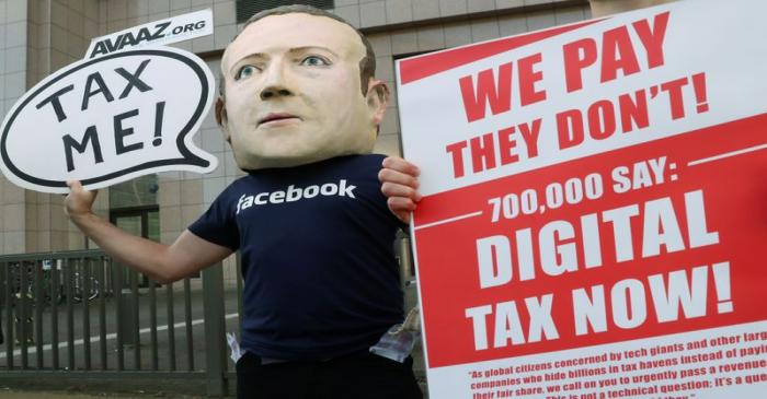 FILE PHOTO: An activist wearing a mask depicting Facebook's CEO Mark Zuckerberg demonstrates