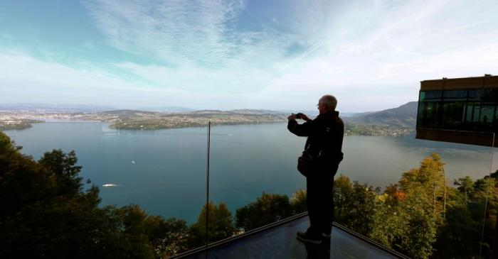 FILE PHOTO: Man takes a picture of Lake Lucerne from a terrace at the Buergenstock resort