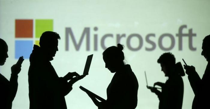 Silhouettes of laptop and mobile device users are seen next to a screen projection of Microsoft
