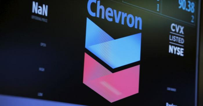 The logo of Chevron is shown on a monitor above the floor of the New York Stock Exchange in New