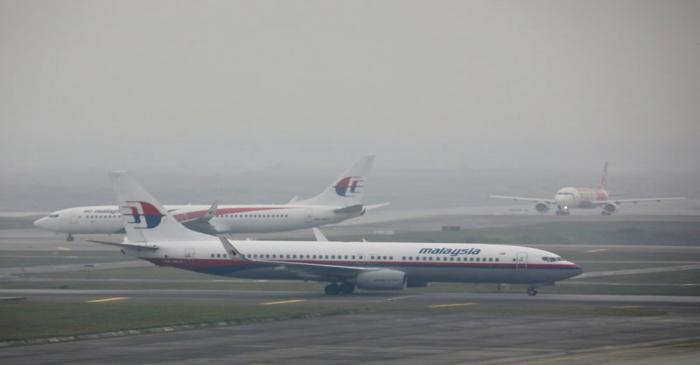 FILE PHOTO: Malaysia Airlines airplanes are pictured on the haze-shrouded tarmac at Kuala