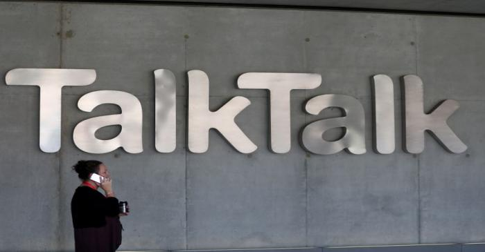 A woman speaks on her phone as she passes a branded logo outside the Talktalk headquarters in