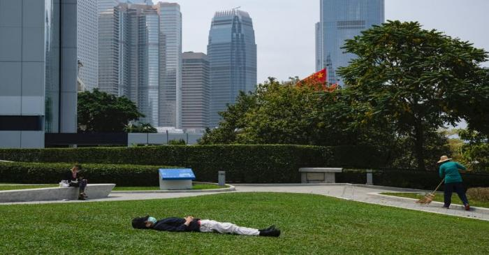 FILE PHOTO: A man with a protective face mask takes a nap during lunch breaks at the financial