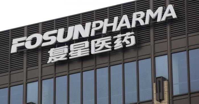 A man walks in front of the headquarters of Shanghai Fosun Pharmaceutical Group in Shanghai