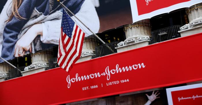 FILE PHOTO: The U.S. flag is seen over the company logo for Johnson & Johnson to celebrate the