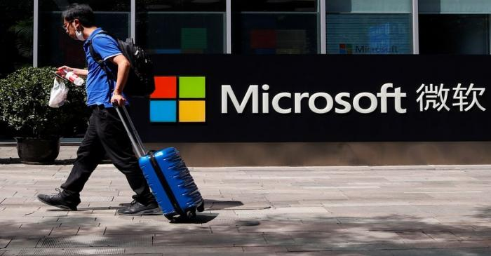 FILE PHOTO: A person walks past a Microsoft logo at the Microsoft office in Beijing