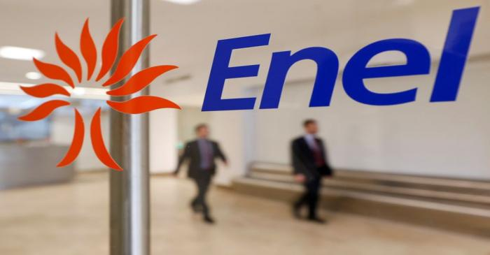 FILE PHOTO: People walk past the logo of Italy's biggest utility Enel at their Rome
