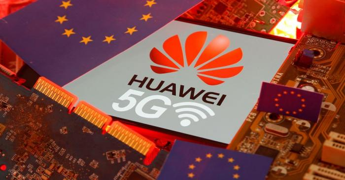 The EU flag and a smartphone with the Huawei and 5G network logo are seen on a PC motherboard