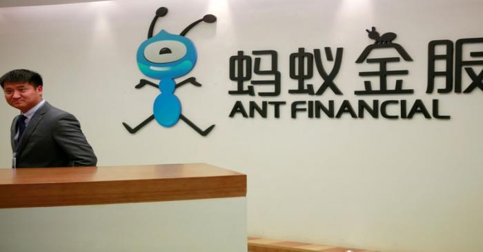 FILE PHOTO: Employee stands next to the logo of Ant Financial Services Group at its