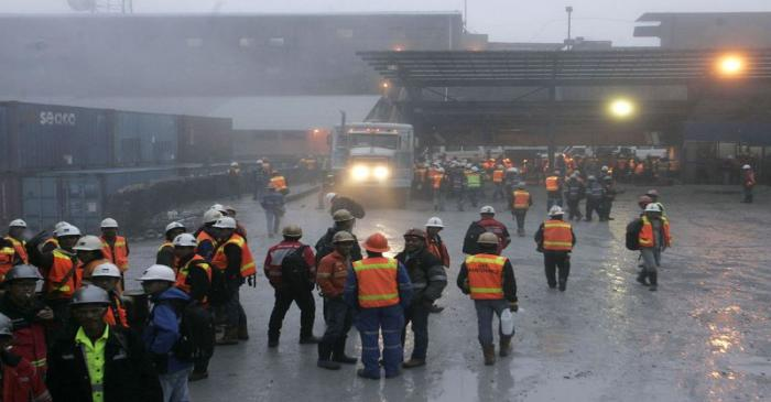 FILE PHOTO: Freeport workers gather around security gate at at Grasberg mine area in