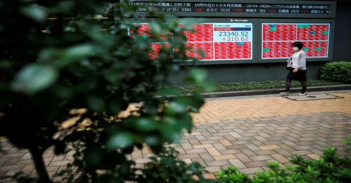 A passersby wearing a protective face mask walks in front of a stock quotation board, amid the