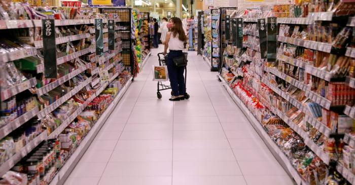 A shopper wearing a protective mask pushes a shopping cart at Japan's supermarket group Aeon's