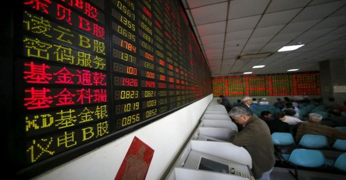 FILE PHOTO: Investors look at computer screens showing stock information at a brokerage house