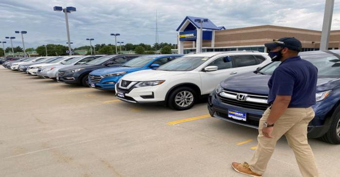 FILE PHOTO: Brandon Parrum, general manager of CarMax's Des Moines store, walks past vehicles