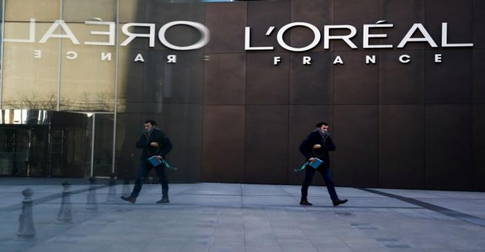 A man walks by the logo of French cosmetics group L'Oreal in the western Paris suburb of