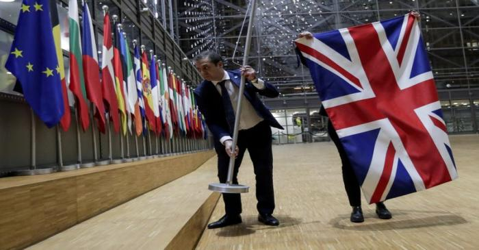 FILE PHOTO: Officials remove the British flag at EU Council in Brussels