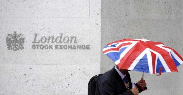 FILE PHOTO: A worker shelters from the rain as he passes the London Stock Exchange in the City