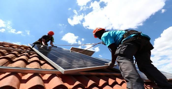 Kauahou and Navarro, workers of the installation company Alromar, set up solar panels on the