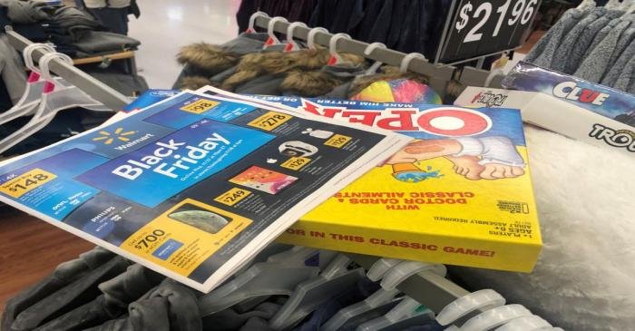 FILE PHOTO: Black Friday ads lay on top of clothes during a sales event on Thanksgiving day at