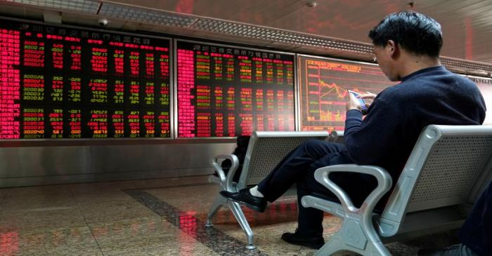 An investor uses his mobile phone in front of a stock quotation board at a brokerage office in