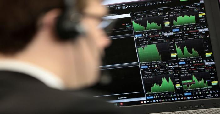 FILE PHOTO: A broker looks at financial information on computer screens on the IG Index the