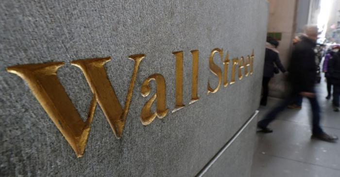 FILE PHOTO: A street sign, Wall Street, is seen outside New York Stock Exchange (NYSE) in New
