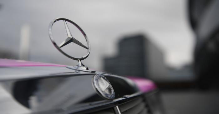 The Mercedes-Benz logo is seen on a car in front of the Mercedes-Benz Museum in Stuttgart