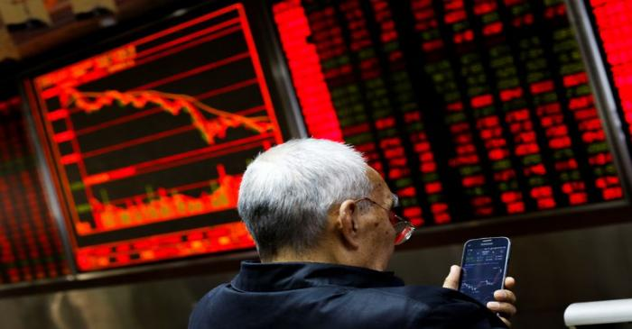 An investor sits in front of a board showing stock information at a brokerage office in Beijing