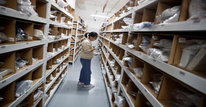 Staff member collects an order from the shelves at the warehouse of the second-hand luxury