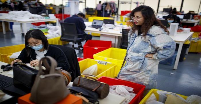 Xu Wei, founder of second-hand luxury goods retail platform Plum, talks to a staff member in