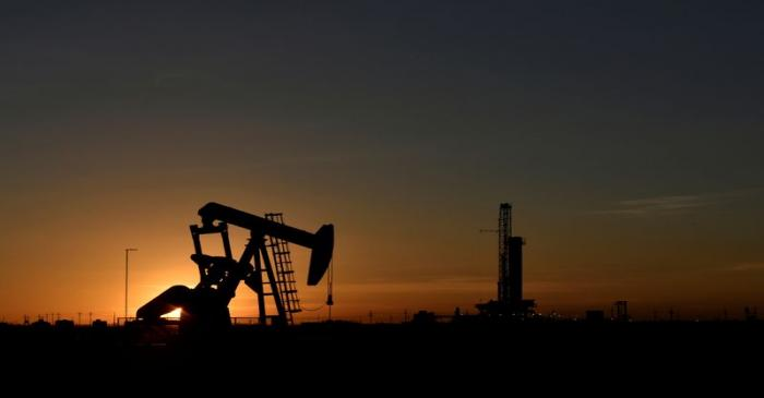 FILE PHOTO: A pump jack operates in front of a drilling rig at sunset in an oil field in