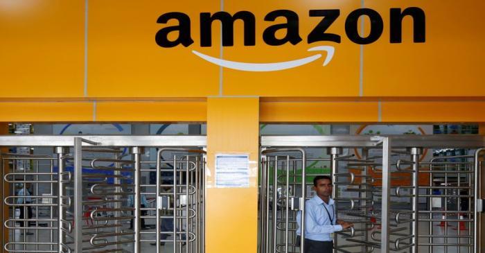 FILE PHOTO: An employee of Amazon walks through a turnstile gate inside an Amazon Fulfillment