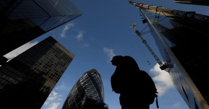A worker walks past office skyscrapers in the City of London financial district, London,